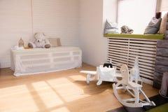 Avião e cavalos de madeira do brinquedo no assoalho na sala Foto de Stock