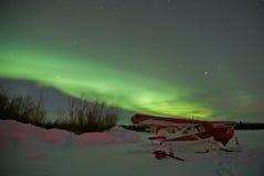 Avião estacionado na neve sob luzes do norte Foto de Stock