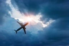 Avião na obscuridade - céu azul e nuvem no raio de sol fotografia de stock royalty free