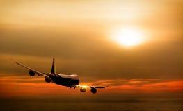 Avião no céu no por do sol Fotos de Stock Royalty Free