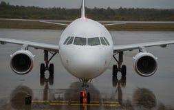 Avião no terminal de aeroporto de aproximação da chuva Foto de Stock