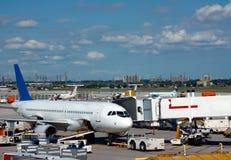 Avião perto de um terminal Fotos de Stock Royalty Free