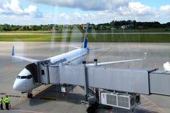 Avião perto de um terminal no aeroporto internacional, vista através de uma janela Imagem de Stock