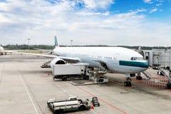 Avião que está sendo prestado serviços de manutenção na porta de um aeroporto internacional Fotografia de Stock Royalty Free
