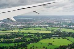 Avião que voa sobre campos verdes perto Londres foto de stock