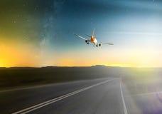 Avião que voa sobre a estrada Foto de Stock