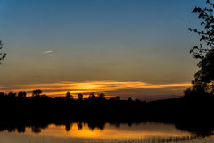 Avião que voa sobre o lago no por do sol imagens de stock royalty free