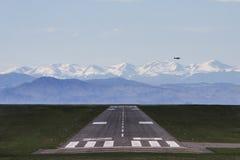 Avião que voa sobre uma pista de decolagem Foto de Stock Royalty Free