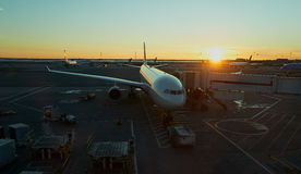 Avión atracado en el aeropuerto en puesta del sol Imagen de archivo