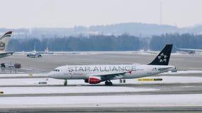 Avión austríaco en las puertas terminales, aeropuerto de Star Alliance de Munich almacen de metraje de vídeo