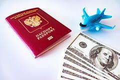 Avión azul del juguete, pasaporte internacional ruso y dólares del efectivo en el fondo blanco Viaje, migración y concepto que de fotografía de archivo
