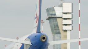 Avión blanco grande del avión de pasajeros en pista en el aeropuerto en un día soleado Plano en el cauce Visión trasera almacen de video