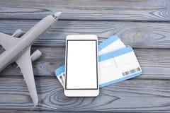 Avión, boletos, smartphone con una pantalla blanca en un fondo de madera imagenes de archivo
