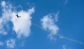 Avión con el rastro colorido en el cielo Fotografía de archivo