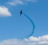 Avión con el rastro colorido en el cielo Fotografía de archivo libre de regalías