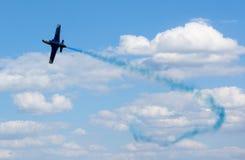 Avión con el rastro colorido en el cielo Imagen de archivo libre de regalías