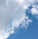 Avión con el rastro colorido en el cielo Imagen de archivo