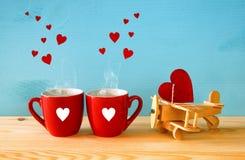 Avión de madera con el corazón al lado de pares de las tazas del coffe Imagen de archivo