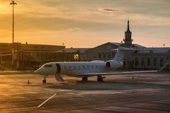 Avión de negocio con la puerta abierta por una escalera en la luz de igualación de oro en el delantal del aeropuerto cerca del te fotografía de archivo