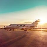 Avión de negocio en el aeropuerto con los rayos del sol Fotografía de archivo