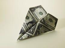 Avión de papel hecho de moneda americana Imagenes de archivo