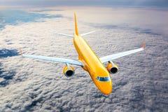 Avión de pasajeros anaranjado en vuelo Foto de archivo