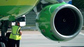 Avión de pasajeros comercial que es comprobado antes del vuelo por los personales del aeropuerto Imágenes de archivo libres de regalías