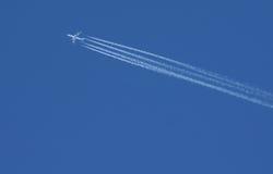 Avión de pasajeros con las estelas de vapor Imagen de archivo