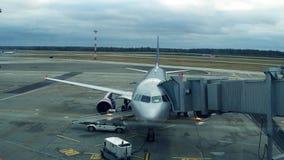 Avión de pasajeros de plata moderno con el puente atado del jet en el vídeo del steadicam del aeropuerto 4K metrajes