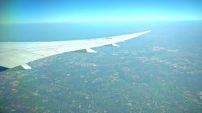 Avión de pasajeros en vuelo Vuelo del ala del ` s del aeroplano sobre la tierra colorida metrajes