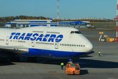 Avión de pasajeros grande y tractor de desvío imágenes de archivo libres de regalías