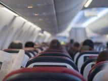 Avión de pasajeros internacional de las líneas aéreas del salón con los pasajeros que leen un periódico Foco borroso fotografía de archivo libre de regalías