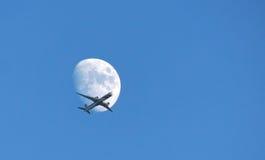 Avión de pasajeros que cruza la luna Imagen de archivo libre de regalías