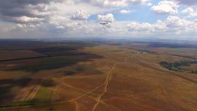 Avión de pasajeros que vuela sobre campos rurales y metrajes
