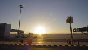 Avión de reacción en pista del aeropuerto como silueta delante de la puesta del sol grande 4K UltraHD almacen de metraje de vídeo