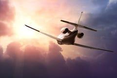 Avión de reacción privada en el cielo en la puesta del sol Fotos de archivo libres de regalías