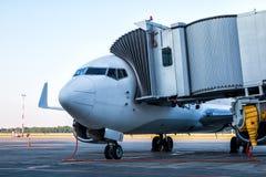 Avión del avión de pasajeros del primer parqueado a un puente del embarque y conectado con una fuente de la alimentación externa imagen de archivo libre de regalías