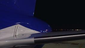 Avión en el aeropuerto de la noche que aguarda el despegue, viaje con el bajo costo, jet privado metrajes