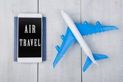 avión, pasaporte y smartphone con el texto y x22; Aire Travel& x22; en la tabla de madera blanca Fotografía de archivo libre de regalías