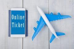 avión, pasaporte y smartphone con el texto y x22; Ticket& en línea x22; en la tabla de madera blanca Fotos de archivo libres de regalías