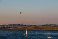 Avión que asciende sobre el velero Fotografía de archivo
