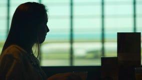 Avión que espera de la mujer hermosa para en restaurante del aeropuerto y café de consumición almacen de metraje de vídeo