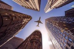 Avión sobre edificios de highrise Fotografía de archivo libre de regalías