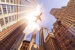 Avión sobre edificios de highrise Imagenes de archivo
