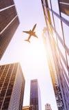 Avión sobre edificios de oficinas modernos Fotografía de archivo libre de regalías