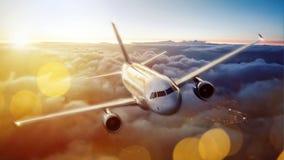 Avión sobre las nubes durante puesta del sol Fotos de archivo libres de regalías