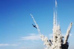 Avión y explosión en el cielo azul Fotos de archivo