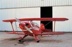 Avión y hangar rojos en aeródromo Fotografía de archivo libre de regalías