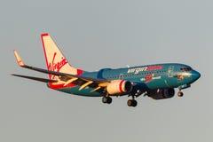 Aviões Boeing 737-7FE VH-VBY das linhas aéreas de Virgin Blue 50th na aproximação à terra no aeroporto internacional de Melbourne Imagens de Stock