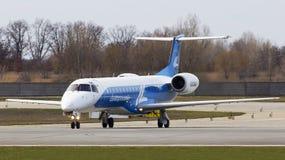 Aviões de Dniproavia Embraer ERJ-145 que correm na pista de decolagem Fotografia de Stock Royalty Free